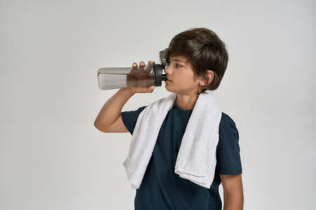 Little sportive boy child in sportswear drinking water from the bottle while standing with white towel around his neck isolated over white background