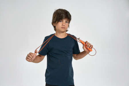 Little sportive boy child in sportswear looking at camera, holding jump rope while standing isolated over white background