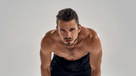 Young shirtless caucasian muscle man standing bent over 版權商用圖片