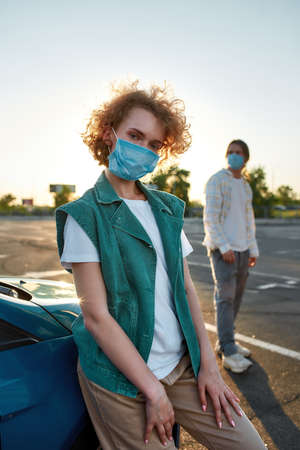A cool-looking redhead young woman leaning against a car wearing mask looking into a camera standing outside on a parking site with her friends on a background