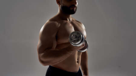 Blacked figure of young muscular athlete lifting dumbbell