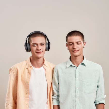 Two young caucasian twin brothers in casual wear listening music in headphones and wireless earphones, while standing isolated on beige background 免版税图像