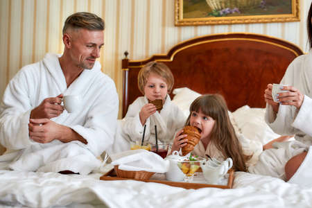 Best breakfast. Parents and two kids in white bathrobes having breakfast in bed, eating pastries and drinking coffee in luxurious hotel room. Family, resort, room service concept