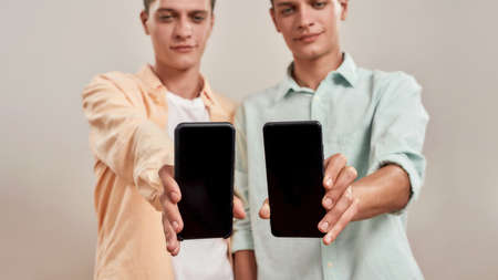 Two young caucasian twin brothers in casual wear holding smartphone with blank screen while standing isolated over beige background 免版税图像