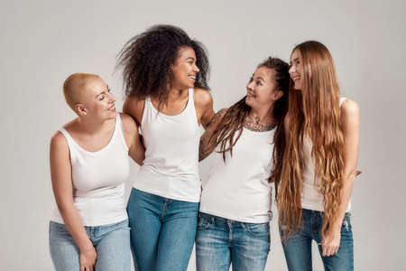 Portrait of four young diverse women wearing white shirts and denim jeans smiling at each other while posing, standing together isolated over grey background
