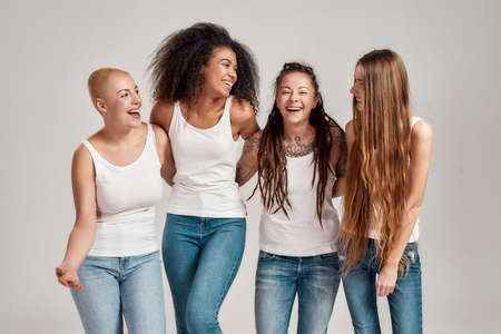 Portrait of four young diverse women wearing white shirts and denim jeans laughing together while posing, standing isolated over grey background