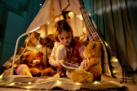 A little girl wearing pyjamas sitting on a floor barefoot in a self-made hut made of a plaid putting her tablet into teddybears fluffy paws with garlands around
