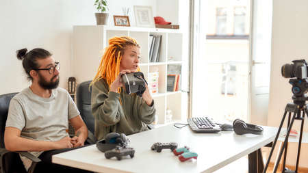 Woman with dreadlocks holding vr glasses. Young male and female technology blogger recording video blog or vlog about new gadgets at home