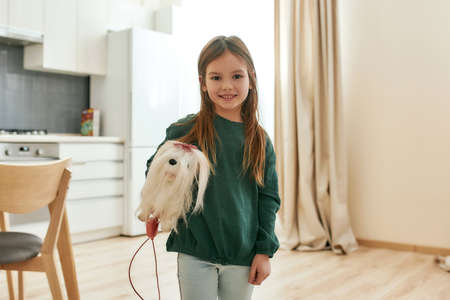 A little girl holds a toy dog under her arm looking into a camera smiling