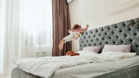 A small girl jumping and falling like a star on a bed barefoot with a teddybear lying around 免版税图像
