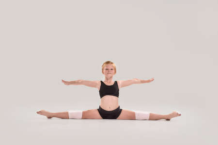 Full length shot of cute little redhead girl child looking at camera, doing splits, showing flexibility isolated over grey background 免版税图像