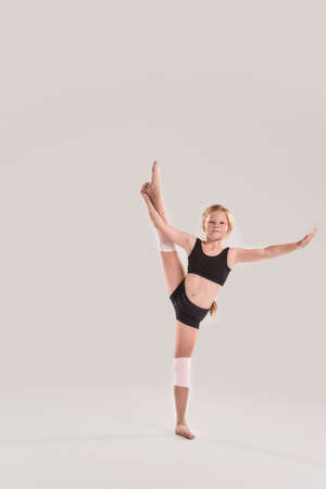 Full length shot of cute little redhead girl gymnast looking at camera, raising one leg with her hand, showing flexibility isolated over grey background 免版税图像