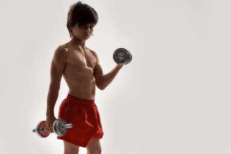 Little sportive boy child with muscular body looking at camera, showing his muscles, lifting weights while standing isolated over white background