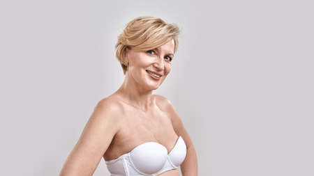Portrait of beautiful middle aged woman in white bra smiling at camera, posing isolated against grey background. Beauty concept 免版税图像