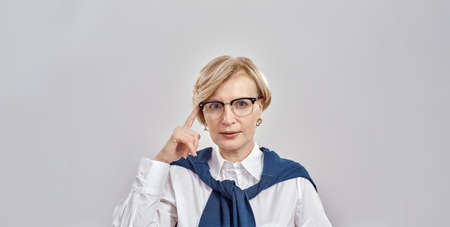 Portrait of elegant middle aged caucasian woman wearing business attire touching her glasses with one finger, looking at camera while standing isolated over grey background 免版税图像