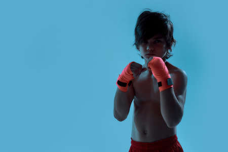 Silhouetted shot of little boy boxer in shorts with boxing bandage on hands, looking at camera ready to fight while posing, standing isolated over blue background