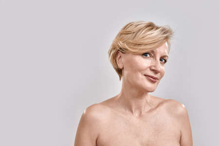 Portrait of beautiful naked middle aged woman looking at camera while posing isolated against grey background. Beauty, skincare concept