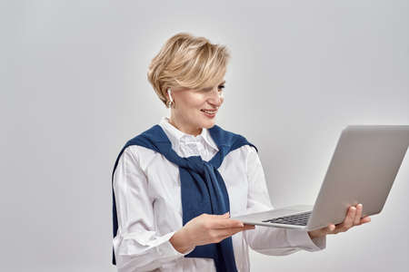 Portrait of elegant middle aged caucasian woman wearing business attire holding and using laptop, standing isolated over grey background