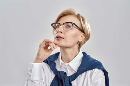 Portrait of elegant middle aged caucasian woman wearing business attire and glasses having a serious, thoughtful look while posing isolated over grey background