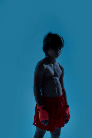 Silhouetted shot of little boy boxer in shorts with boxing bandage on hands, looking at camera while posing, standing isolated over blue background