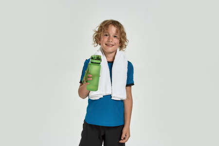 Portrait of little sportive boy child in sportswear smiling at camera, holding water bottle while standing with towel around his neck isolated over white background