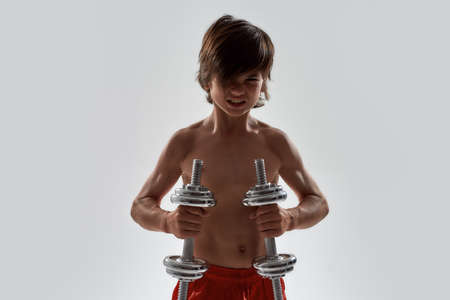 Little sportive boy child with muscular body looking emotional while exercising, lifting weights, standing isolated over grey background