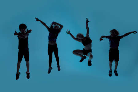 Silhouetted full length shot of four little sportive kids looking joyful while posing, jumping isolated over blue background