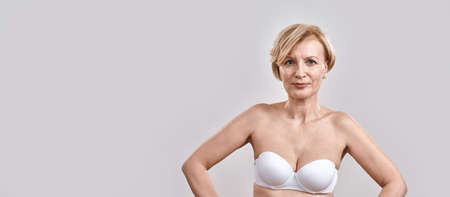 Portrait of beautiful middle aged woman in white bra looking at camera, posing isolated against grey background. Beauty concept 免版税图像