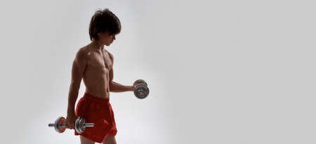 Little sportive boy child with muscular body exercising, showing his muscles, lifting weights while standing isolated over grey background