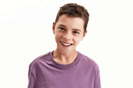 Close up portrait of happy teenaged disabled boy with cerebral palsy smiling at camera, posing isolated over white background
