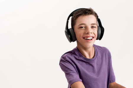 Close up portrait of happy teenaged disabled boy with cerebral palsy in headphones smiling at camera, using his walker isolated over white background