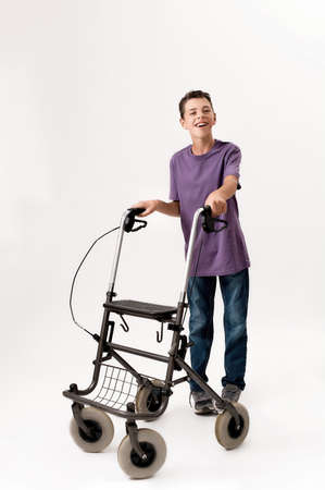 Full length shot of happy teenaged disabled boy with cerebral palsy smiling at camera, taking steps with his walker isolated over white background