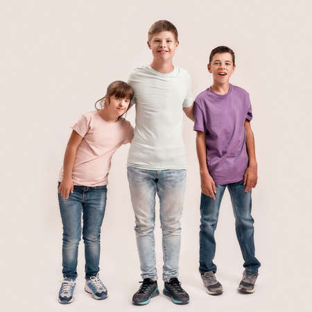 Full length shot of three cheerful teenaged disabled children with Down syndrome and cerebral palsy smiling while standing together isolated over white background