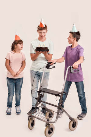 Full length shot of teenaged disabled boy holding cake while celebrating his birthday together with friends in birthday caps, standing isolated over white background Stockfoto