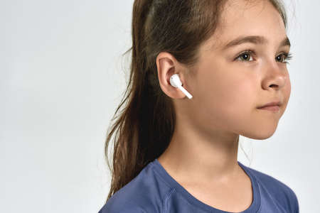 Close up portrait of little sportive girl child wearing earphones, listening to music, looking away while posing isolated over white background