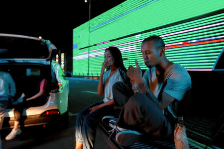 A group of two young casually dressed dark-skinned friends of different genders sitting in an opened car trunk lighting their cigarettes with a led screen and cars behind