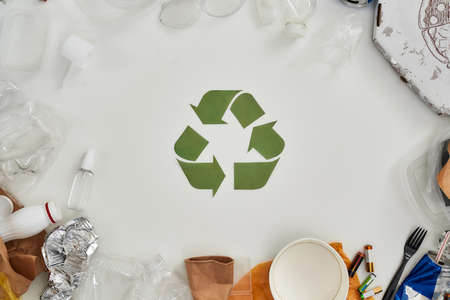 Happiness is recycling. Flatlay composition with different waste, garbage types and recycling sign made of paper in the center over white background Standard-Bild