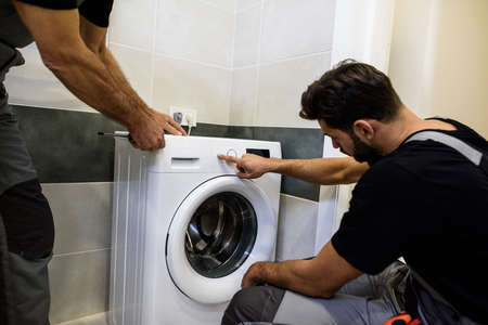 Two repairmen, workers in uniform working, reading washing symboles on washing mashine before fixing it, holding screwdriver in the bathroom. Repair service concept Reklamní fotografie