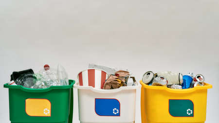 Set of three colorful green, yellow and white recycle garbage bins with recycle sign on it full of rubbish isolated on white background. Waste separation concept