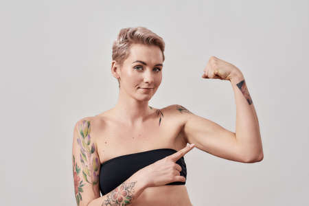 Touch It. Portrait of half naked tattooed woman with short hair looking at camera, pointing at her strong muscle, biceps isolated over light background