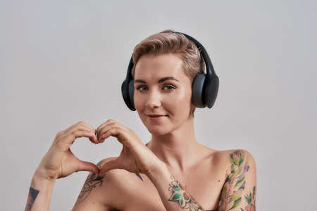 Attractive tattooed woman with pierced nose and short hair in headphones looking at camera, showing heart with hands while listening to music isolated over grey background Stock Photo