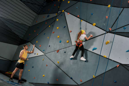 Male instructor holding rope, teaching, looking at girl in safety equipment and harness while she is training on the artificial climbing wall