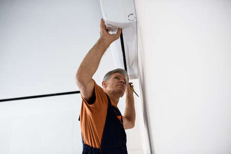 Aged worker in uniform, air conditioning master installing a new air conditioner in the apartment. Construction, maintenance and repair concept