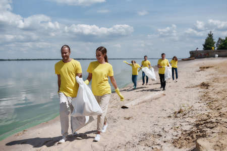 Two young happy eco activists in uniform and rubber gloves carrying trash bags and discussing something while cleaning the beach with group of volunteers