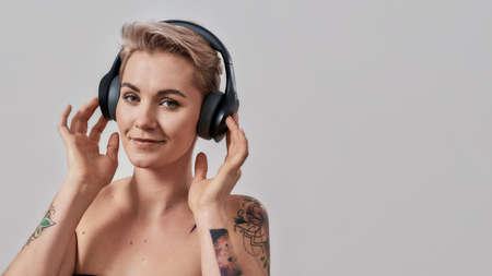Attractive tattooed woman with pierced nose and short hair in headphones looking at camera while enjoying listening to music isolated over grey background Stock Photo
