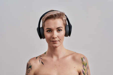 Attractive tattooed woman with pierced nose and short hair in headphones looking at camera while listening to music isolated over grey background