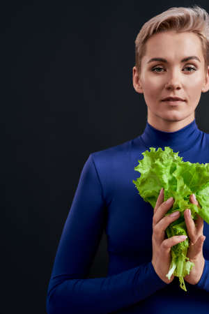 Cropped portrait of attractive woman with pierced nose and short hair in blue turtleneck looking at camera, holding fresh green lettuce isolated over dark background Stock Photo