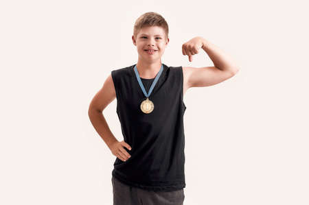 Proud disabled boy with Down syndrome wearing gold medal smiling at camera, raising clenched fist, feeling strong while posing isolated over white background