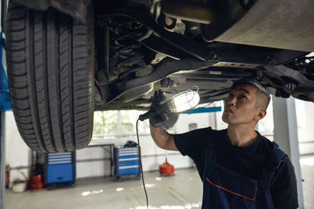 Asian mechanic examining auto bottom with flashlight