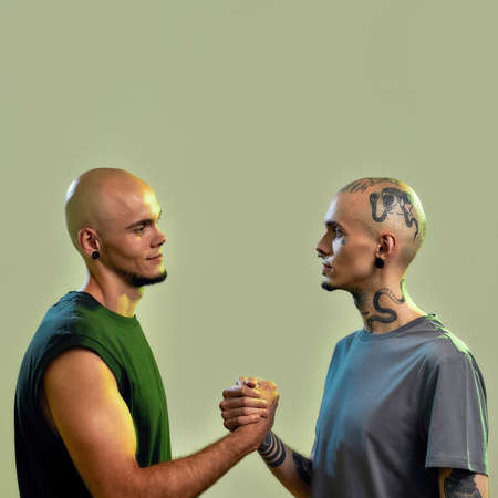 Portrait of young twin brothers with tattoos and piercings looking at each other, holding hands, standing face to face isolated over light green background